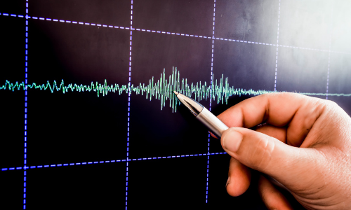 A scientist analyzes earthquake graph data on a monitor.